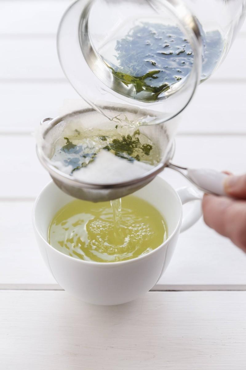 Ein Mann gießt grünen Tee auf