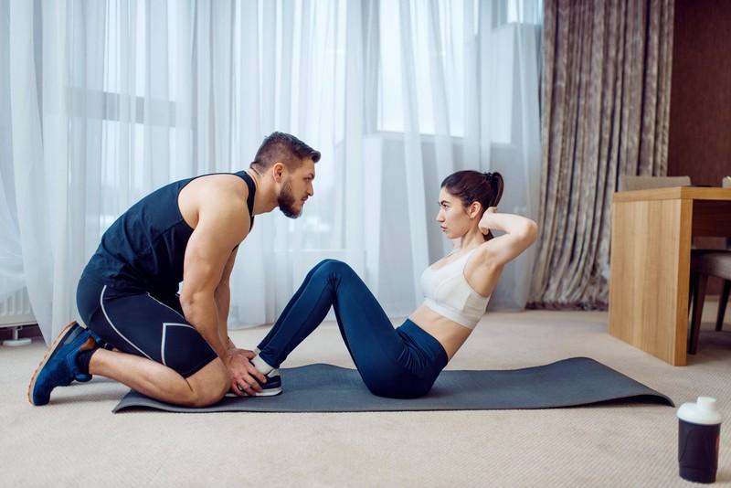 Der Mann trainiert mit seiner Freundin zuhause.