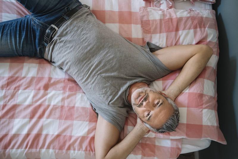 Ein Mann liegt entspannt im Bett